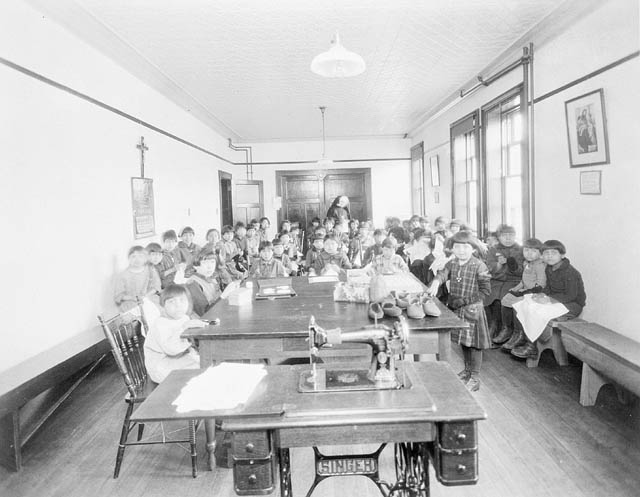Mi'kmaq girls in sewing class at the Roman Catholic-run Shubenacadie Indian Residential School in Shubenacadie. (Photo via Library and Archives Canada, Online MIKAN no. 3193832)