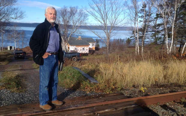 Mike Johnson, head of the CB Railway Victims Association stands near his unintentionally off-the-grid home. (Photo by Joan Weeks/CBC http://www.cbc.ca/news/canada/nova-scotia/genesee-wyoming-rail-fees-undeveloped-bras-dor-lake-1.3861133)