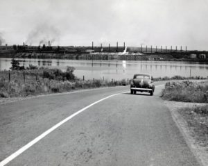 Item is a photograph of a view of the Sydney Steel Plant from Westmount Road, with a car in the foreground. (Beaton Institute, https://www.cbu.ca/campus/beaton-institute/ reference code 77-66-200, circa 1945)