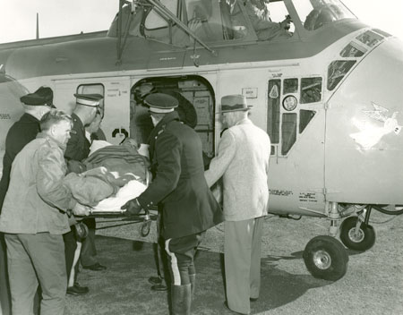 Injured miner being taken to hospital by helicopter. Springhill, 1958. (Photo by Robert Norwood via Nova Scotia Archives https://archives.novascotia.ca/)