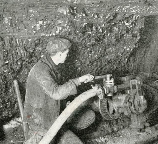 Photographic postcard of a miner operating a long wall machine. (Source: Beaton Institute Digital Archives https://beatoninstitute.com/)