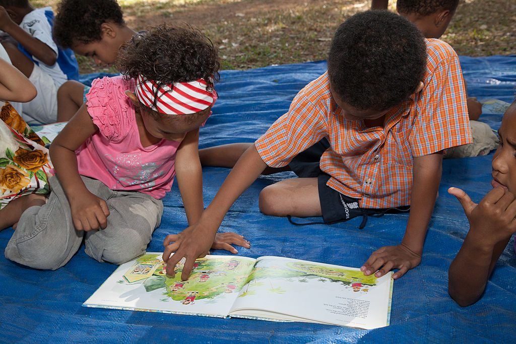 Children at Buk bilong Pikinini (Books for Children), Papua New Guinea. (Photo by Ness Kerson/madNESS Photography for AusAID, CC BY-SA 4.0 http://creativecommons.org/licenses/by-sa/4.0, via Wikimedia Commons