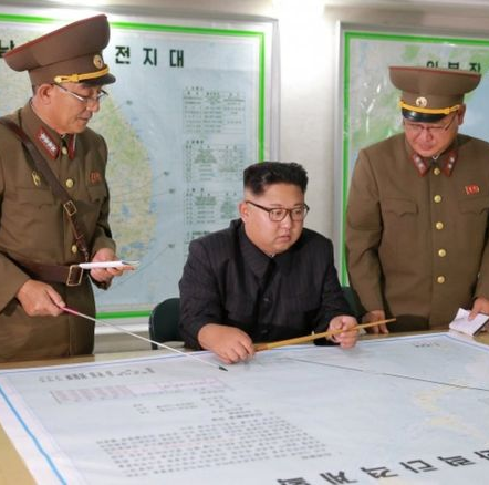 Kim Jong-un briefed by generals. (Image released by North Korean state news agency)