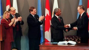Prime Minister Jean Chrétien hands signed landmine treaty to UN Secretary General Kofi Annan in a ceremony in Ottawa with Nobel Prize laureate Jody Williams, left, Foreign Affairs Minister Lloyd Axworthy, centre, and International Committee of the Red Cross President Cornelio Sommaruga. (CP Photo / Tom Hanson)