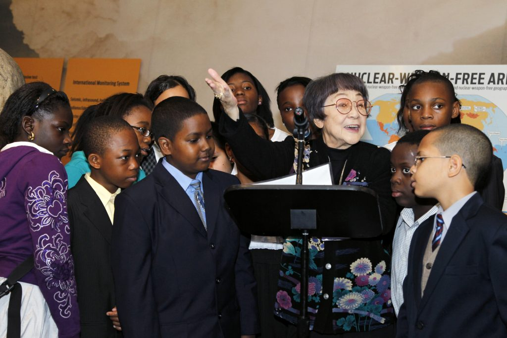 Surrounded by schoolchildren, a Hibakusha, speaks at a special UN event commemorating Disarmament Week (annually 24-30 October). UN Photo
