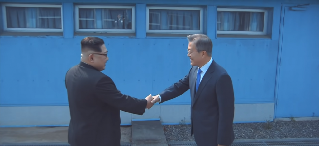 North Korea's Kim Jong-un shakes hands with South Korea's Moon Jae-in across the demarcation line separating their countries. 27 April 2018 (Image via Korea.net Youtube channel)