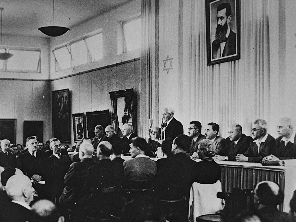 David Ben Gurion flanked by the members of his provisional government reading the Declaration of Independence in the Tel Aviv Museum Hall, 14 May 1948. (Government Press Office (Israel) [CC BY-SA 3.0 (https://creativecommons.org/licenses/by-sa/3.0)], via Wikimedia Commons)