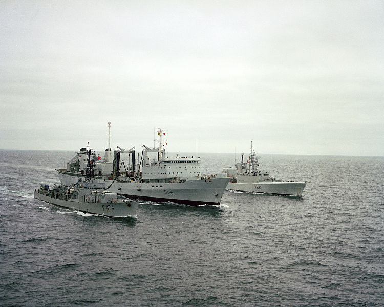 starboard bow view of the Canadian replenishment ship HMCS Protecteur (AOR 509) refueling the Canadian destroyer escort HMCS Nipigon (DDH 266) off its port side and the Portuguese frigate Almirante Magalhaes Correa (F 474) off its starboard side. 1982. (Photo by US Armed Forces via Wikimedia Commons)