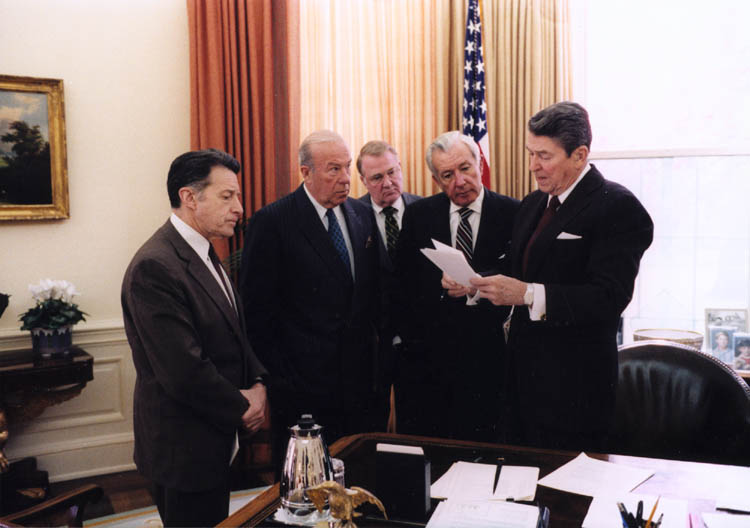 President Ronald Reagan with Caspar Weinberger, George Shultz, Ed Meese, and Don Regan discussing the President's remarks on the Iran-Contra affair, Oval Office. 25 November 1986.