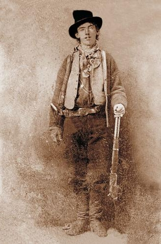 Portrait of American gunman Billy the Kid (1859–1881). Image mirrored on vertical axis to correct widely-seen flopped tintype. Cartridge loading gate on Winchester Model 1873 lever action rifle is on the right side of the receiver. (Ben Wittick 1845–1903, Public Domain, via Wikimedia Commons)