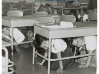 "P.S. 58 - Carroll & Smith Sts. Bklyn. hold a ""take cover"" drill practice Here youngsters crawl under their desks, 1962, photo by Walter Albertin"