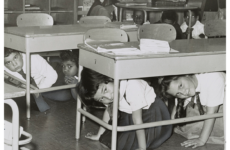 """P.S. 58 - Carroll & Smith Sts. Bklyn. hold a """"take cover"""" drill practice Here youngsters crawl under their desks, 1962, photo by Walter Albertin"""