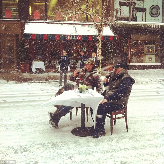 Men sitting at a table on a snowy street in NYC