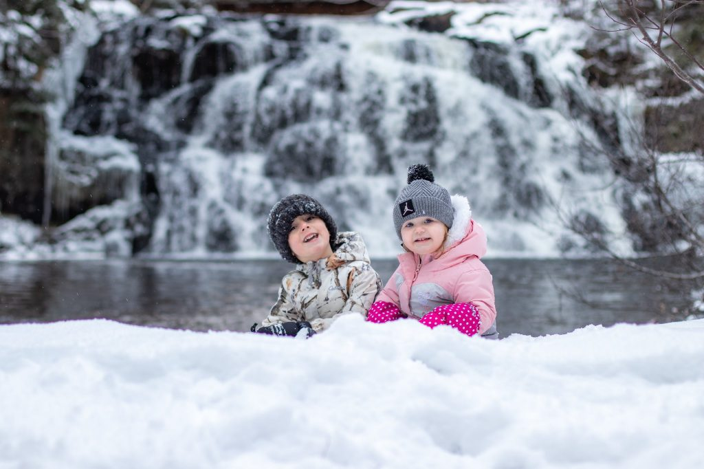Children in front of waterfall in Winter.