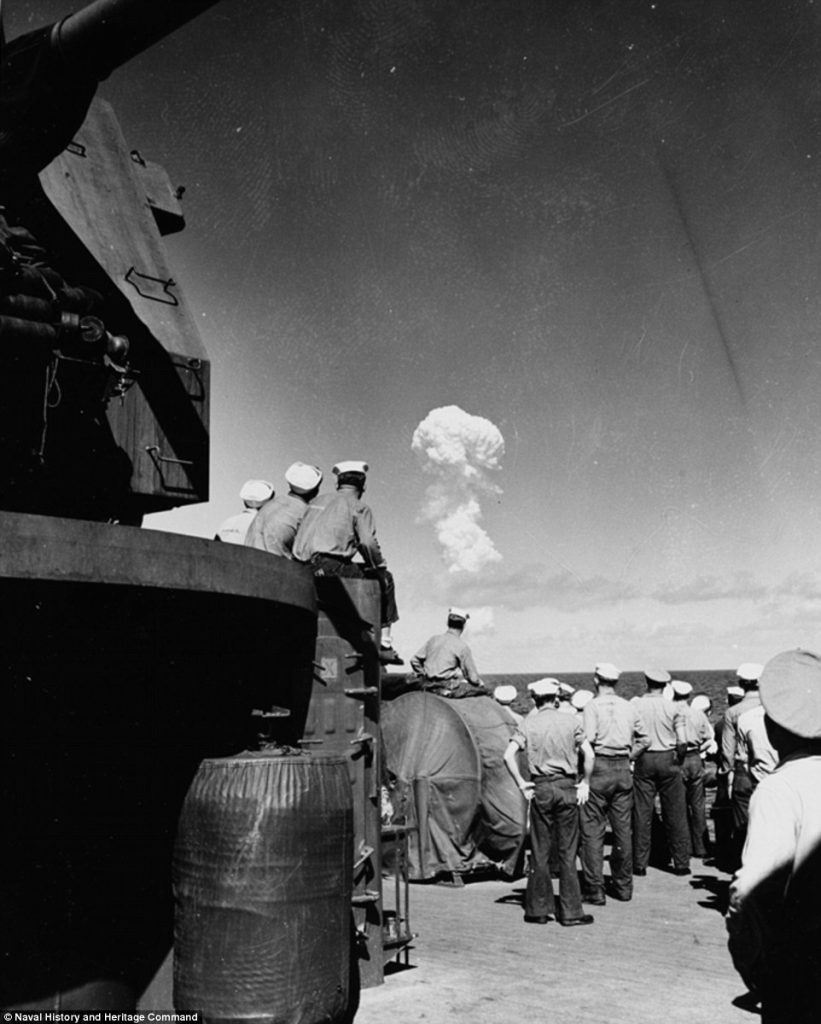 American sailors watch the 'Able Test' burst miles out to sea from the deck of the support ship USS Fall River on 1 July 1946.